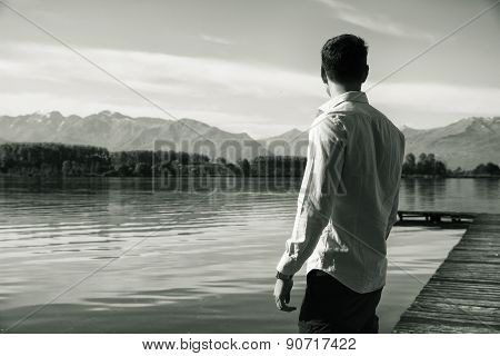 Attractive young man on a lake in a sunny, peaceful day