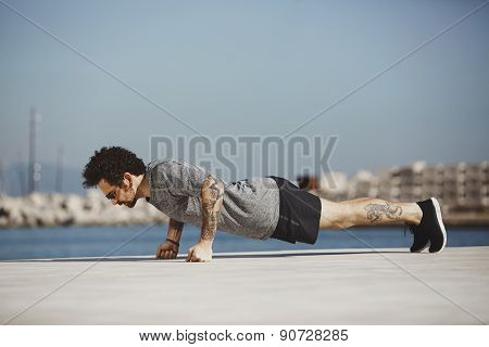 Sport Fitness Man Doing Push Ups. Male Athlete Exercising Push Up Outside In Sunny Sunshine.