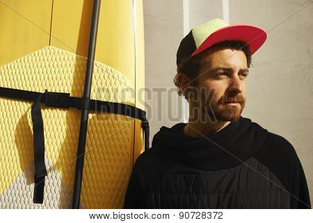Surfer Sports Man Wearing A Neoprene Rubber Diving Suit At City Wall And Looking At The Horizon.