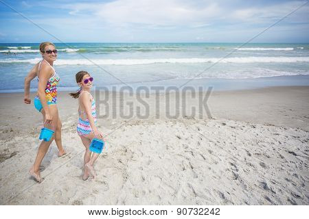 Mother and daughter playing together in the sand on a beautiful beach day. They are running with buckets in hand ready to build something fun together. Lots of copy space
