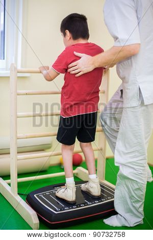 physician supports a child standing on the training platform
