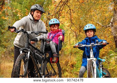 Family on bikes in autumn park, father and kids cycling, active family sport outdoors