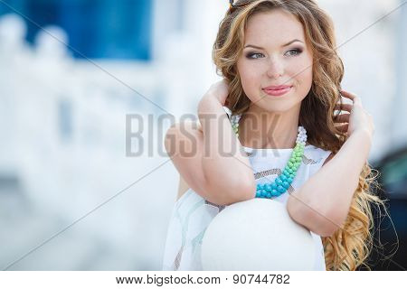 Portrait of young smiling beautiful woman in town in the summer.
