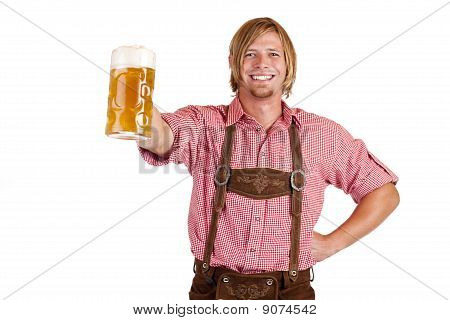 Happy smiling man with leather trousers (lederhose) holds oktoberfest beer stein