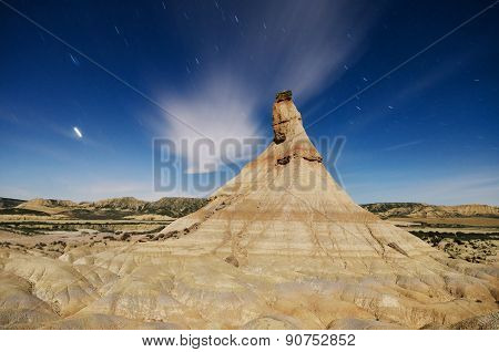 Scenic view of a desertic landscape at night with star trails in Bardenas reales Navarra Spain. poster