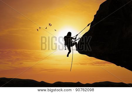 Silhouette Of Woman Climbing On Rock