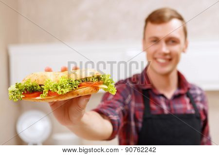 Smiling man showing done sandwich