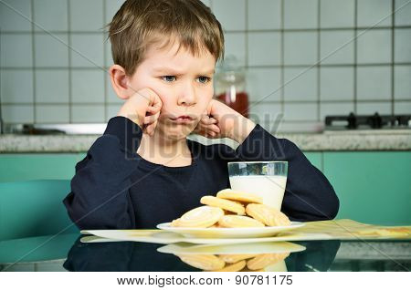 Angry little boy sitting at the dinner table. biscuits on the table and a glass of milk. the boy did not want to eat the food. green and gray kitchen furniture in the background. horizontal poster