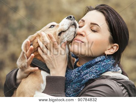Woman tenderly hugs her dog