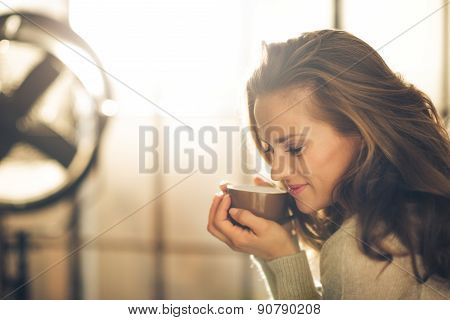 Closeup Of Smiling Brunette Holding And Smelling Hot Coffee