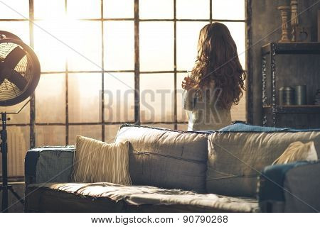 Brunette Looking Out Of Urban Loft Window