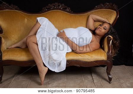 Pregnant woman in white dress reclining on a couch