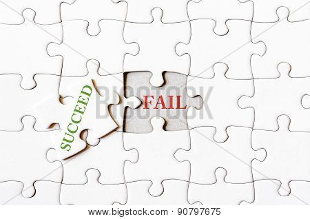 Missing jigsaw puzzle piece with word SUCCEED covering text FAIL. Business concept image for completing the final puzzle piece. poster