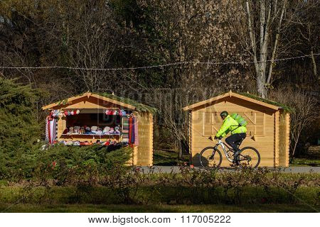 Bucharest Romania - December 26: Herastrau Parc on December 26 2015 in Bucharest. Beautiful and large park with wooden little houses winter nature and bicyclist on Christmas time. poster