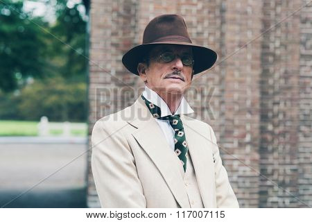 Senior Dandy With Hat And Glasses In Front Of Gate.