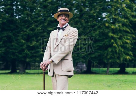 Smiling Wealthy Dandy Standing With Cane In Garden.