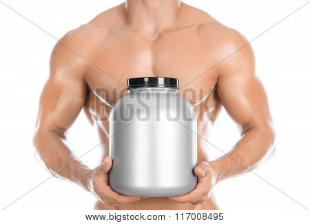 Bodybuilding And Sports Theme: Handsome Strong Bodybuilder Holding A Plastic Jar With A Dry Protein