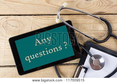 Any questions  - Workplace of a doctor. Tablet, stethoscope, clipboard on wooden desk background. To
