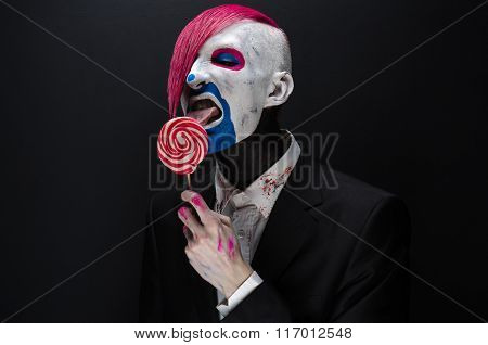 Clown And Halloween Theme: Scary Clown With Pink Hair In A Black Jacket With Candy In Hand On A Dark