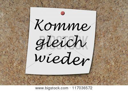 Komme gleich wieder (German Be richt back) written on a memo pinned on a cork board poster