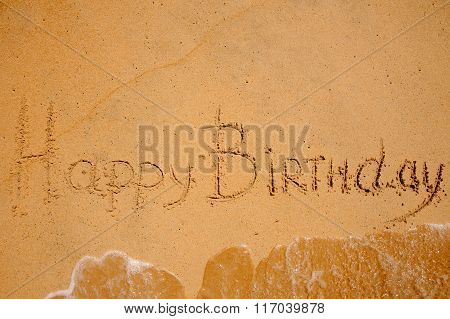 Happy Birthday Sign On The Beach Washed By Wave