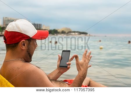Emotional man with phone in his hand on beach in sea resort
