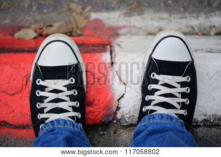 Black Canvas Sneakers On A Sidewalk