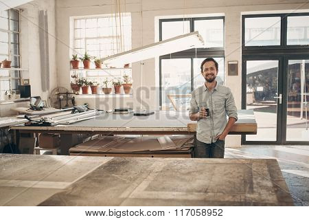 Smiling entrepreneur standing in his workshop with coffee