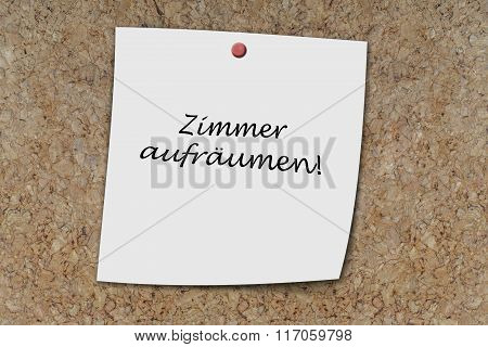 Zimmer aufrдumen (German clean up room) written on a memo pinned on a cork board poster