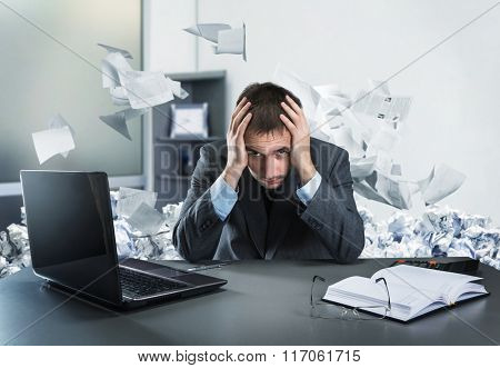 Frustrated businessman holding his head sits in the office