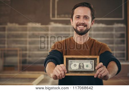 Entrepreneur showing framed bank note with a proud smile