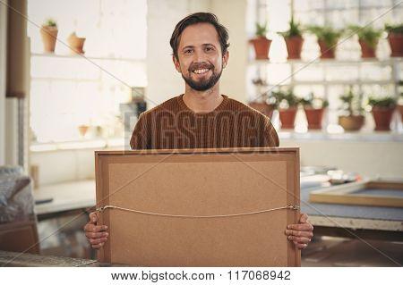 Positive framer smiling his workshop holding a framed item