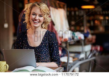 Female Fashion Designer Working At Laptop In Studio