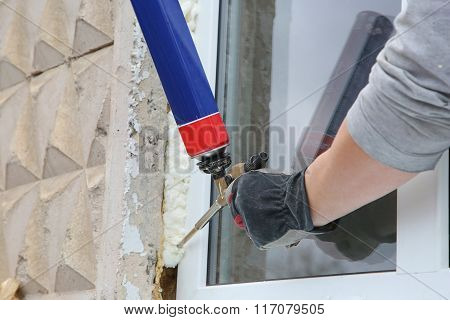 Worker's hand fix a window using polyurethane foam poster