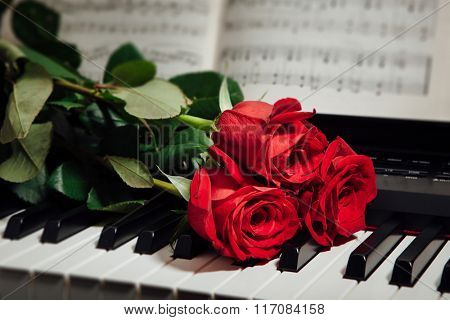 red roses on piano keys and music book