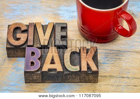 give back word abstract in vintage letterpress wood type printing blocks stained by color inks with a cup of coffee