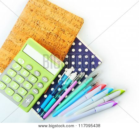 A pile of stylish notebooks and stationary, isolated on white background