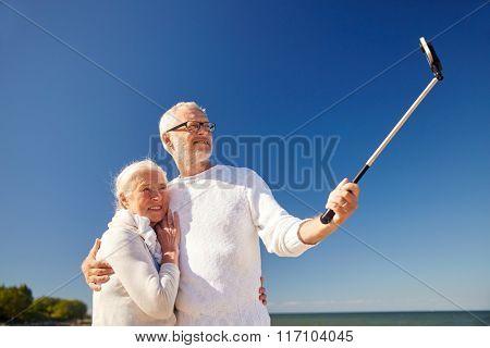 seniors with smartphone taking selfie on beach