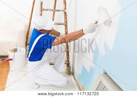 above view of painter with cap and gloves painting a wall with paint roller wooden vintage ladder and bucket on background poster
