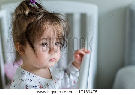 Portrait Of Adorable Little Baby Girl Staying At Her Bed