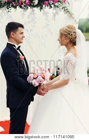 Handsome Elegant Groom And Beautiful Blonde Bride Taking Vows At The Aisle Outdoors