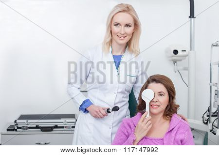 Skillful ophthalmologist is examining human vision in office