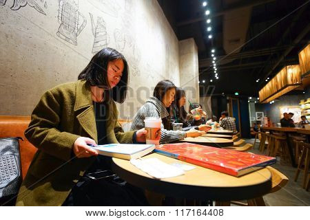 SHENZHEN, CHINA - FEBRUARY 05, 2016: people at Starbucks Cafe. Starbucks Corporation is an American global coffee company and coffeehouse chain based in Seattle, Washington