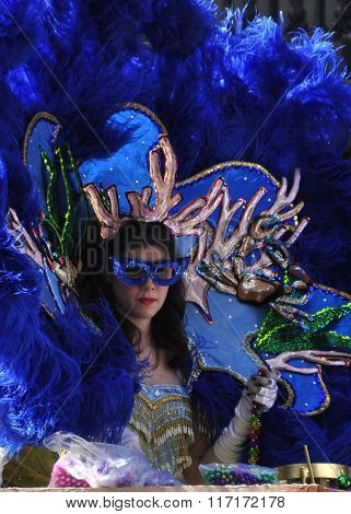 NEW ORLEANS - FEBRUARY 14, 2015: A lady masker in blue on a parade float throws beads
