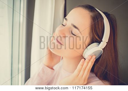 Young womanl enjoying music in headphones at home relaxing. Relaxed student girl listening to music
