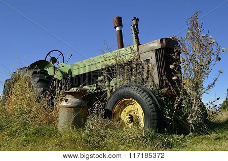 Rusty milk can in front of old green tractor