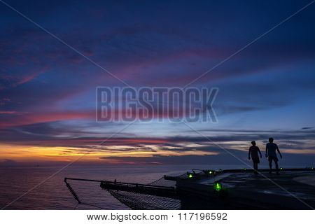 Two men walking on oil rig helipad when sunset time and green edge light on