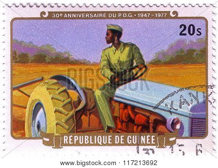 Guinea - Circa 1977: Stamp Printed By Guinea, Shows President Sekou Toure On A Tractor, The 30Th Ann
