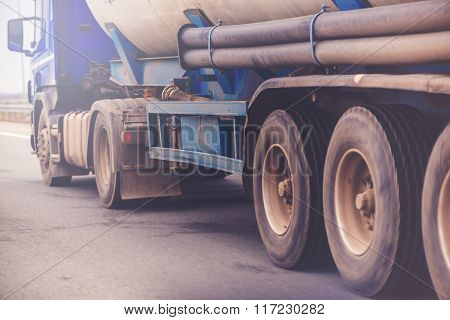 Commercial trailer truck in motion on freeway cargo transportation selective focus on wheels motion blur poster