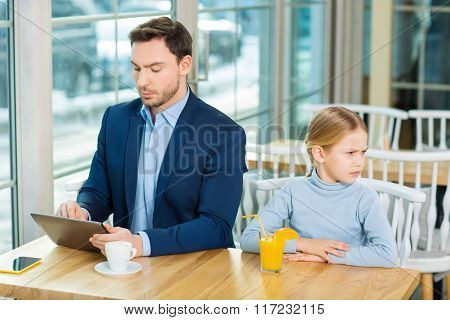 Father and daughter sitting at the cafeteria.
